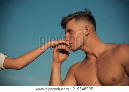 Athlete with muscular chest kiss female hand on sunny day on blue sky. Romance love relations concept. Sport bodybuilding fitness health.