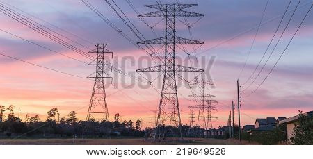 Industrial background group silhouette of transmission towers (or power tower electricity pylon steel lattice tower) at twilight in USA. Texture of high voltage pillar overhead power lines at dusk poster