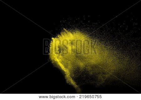Yellow particles explosion on black background. Freeze motion of yellow dust splash on dark background.