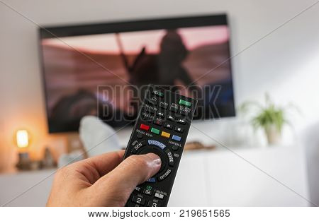 POV-Shot from feeds and a hand holding a TV Remote control to ZAP on tv at home. ideal for websites and magazines layouts
