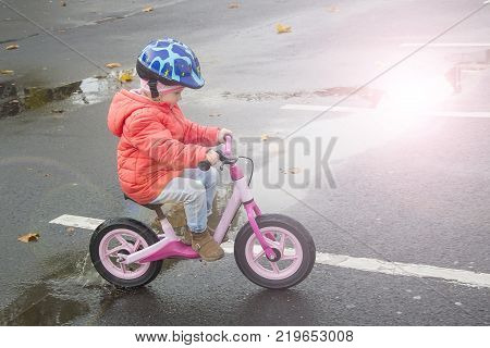 Happy child riding a bicycle in the fall. Cute little girl in safety helmet riding a bike outdoors. Little girl on a red bicycle.