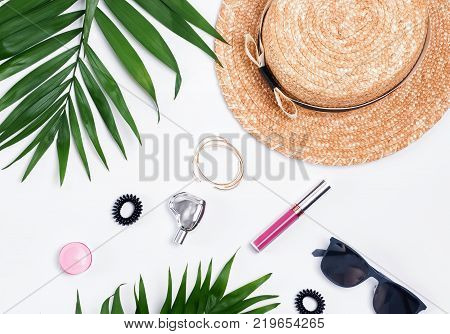 Green leaves and summer feminine acessories on the white background