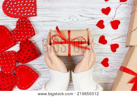 Valentines Day background. girl hand give valentine gift box with a red heart inside on a white old wooden table. Valentine day.