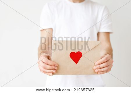 Cropped image of male s hands hold letter with red heart. Unrecognizable male recieves envelop, isolated over white studio background, dressed casually. Folded letter in human s hands.