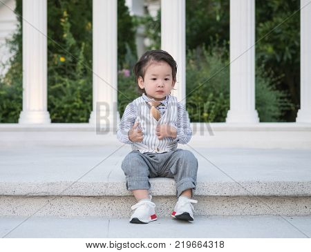 Closeup asian kid sit at the pathway in wedding ceremony background