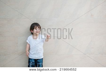 Closeup cute asian kid pointing finger in front of him on marble stone wall textured background with copy space