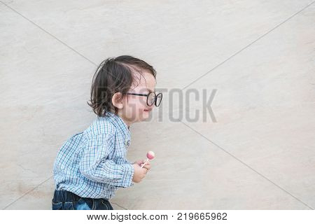 Closeup sad asian kid cry because he want something on marble stone wall textured background with copy space
