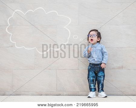 Closeup asian kid say something action with text box on marble stone wall textured background with copy space