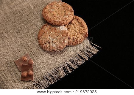 oat cookies and chocolate pieces on canvas tablecloth
