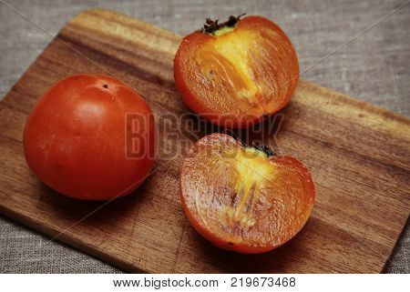 Ripe persimmons slices on wooden cutting board