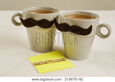 Mutual relations of a male-male. Restart. Symbolic cups of a man-man and the text restart with wooden letters.
