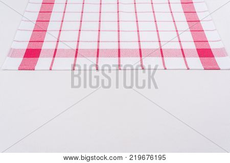 Background for product. Checked tablecloth in a red and white cage on textured surface, view from above