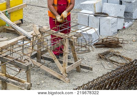Worker At The Construction Site Making Reinforcement Metal