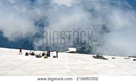 A group of mountain climbers taking a rest on the side of a snowy mountain