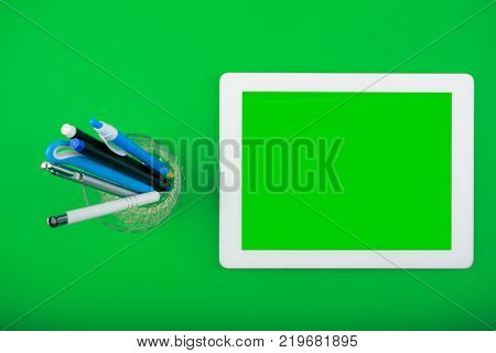 worktop top view. white tablet with a blank screen for copy space and organiser with pens on green background