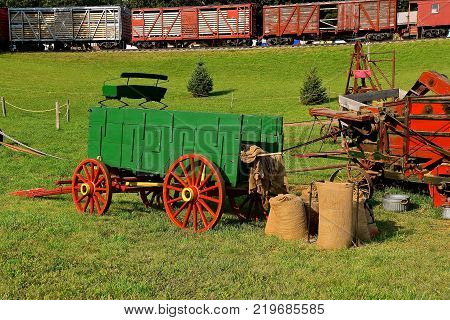 An old freight train passes by a threshing scene with the green wagon box and gunny sacks of harvested wheat.