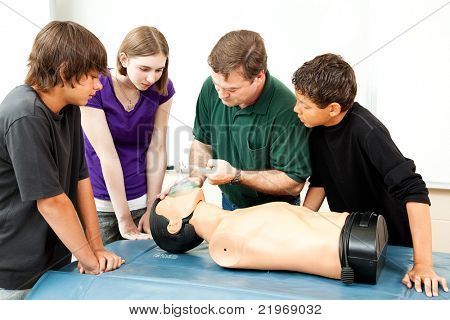 Teacher demonstrates to students how to use an oxygen mask for CPR.