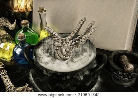 Halloween composition of boiling cauldron mysterious bottles and black magic book.