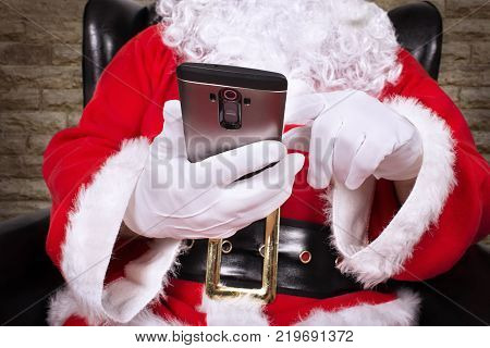 Close up on Santa Claus is holding and touching smartphone.