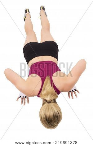 Sporty woman is doing pushups isolated on white background.