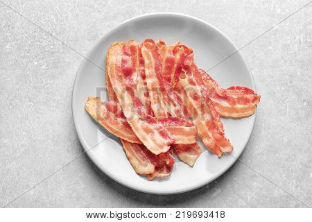 Plate with cooked bacon rashers on table