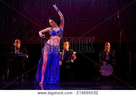 MOSCOW, RUSSIA - OCT 21, 2017: Female participant and orchestra on stage of Luna Theatre during Gala Concert after 12th international festival of oriental dance ASSEMBLY 2017.