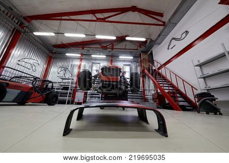 MOSCOW, RUSSIA - OCT 27, 2017: (PR) Technician works with racing car on wheeled rack based on Lotus Seven in garage of DB 527 company producer of russian sports cars .