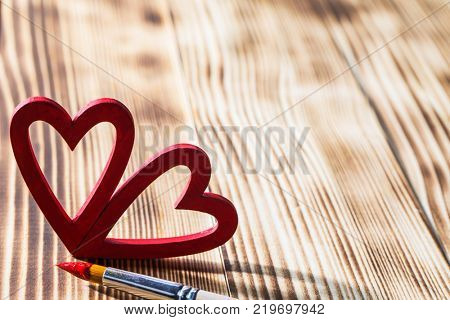 Two wooden red painted Valentine day hearts and paint brush on wooden background