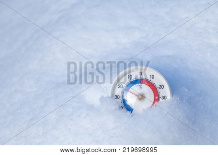 Thermometer with celsius scale placed in a fresh snow showing sub-zero temperature minus twenty one degree a cold winter weather concept