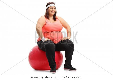 Overweight woman sitting on an exercise ball and looking at the camera isolated on white background