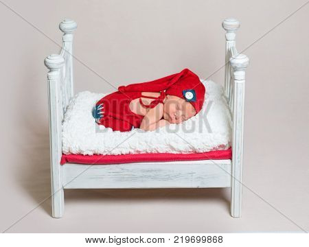 Newborn baby takes a nap on a wooden crib.