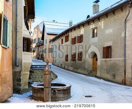 Little street with  typical houses and fountain in the older part of Guarda, Inn District,  Swiss canton of Graubunden, Switzerland.