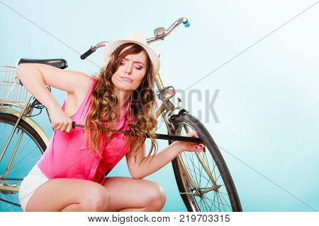 Young woman pumping up tire tyre with bike bicycle pump. Summer recreation activity.