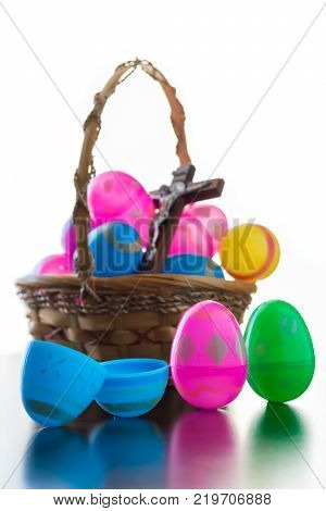 A brown basket is full of decorated easter eggs. A crucifix is among the eggs in the basket. Standing up in front of the basket are three decorated easter eggs. One of the eggs is opened as was the tomb of Jesus. All the items cast a reflection on the tab