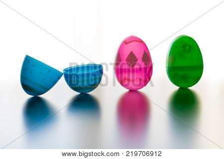 Blue pink and green designed easter eggs are photographed stand up. The blue egg is opened symbalizing Jesus' openned tomb. The eggs cast colored shadows onto the reflective table top. The seemless background is all white.