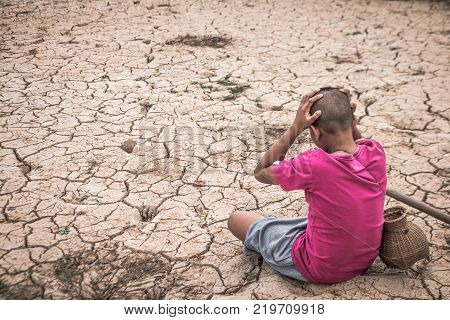 The boy sat on a barren ground with despair Concept drought and crisis environment.