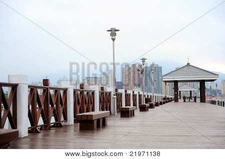 Wooden Boardwalk With Skyscrapers In Background