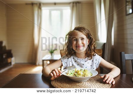 8 years old happy child girl eating pasta at home for lunch or dinner