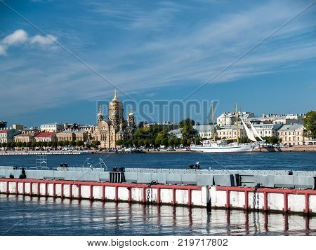 City landscape with a pier for mooring ships on the Promenade des Anglais in Saint Petersburg on the Neva River and a view of Lieutenant Schmidt's embankment with cars a frigate a temple buildings poster