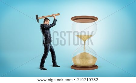 A businessman holds a large heavy hammer ready to hit a large hourglass with half of its sand fallen down. Change circumstances. Bending rules. Business and success.