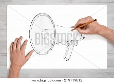 Two male hands in first person view draw a megaphone with a pencil on white paper. Public speaking. Speech preparation. Public relations job.
