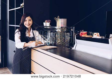 small business owner with notebook at counter in coffee shop. asian female barista wearing apron writing note at bar in cafe. food service restaurant entrepreneur concept.