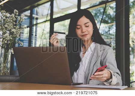 young woman holding a credit card and using smart phone for online shopping at cafe. businesswoman purchase goods from internet at office. female adult make payment on bank website at workplace