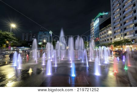 Ho Chi Minh City, Vietnam - December 21st, 2017: Light shimmering fountain at night on a pedestrian street and discolored in the center of Nguyen Hue in Ho Chi Minh City, Vietnam