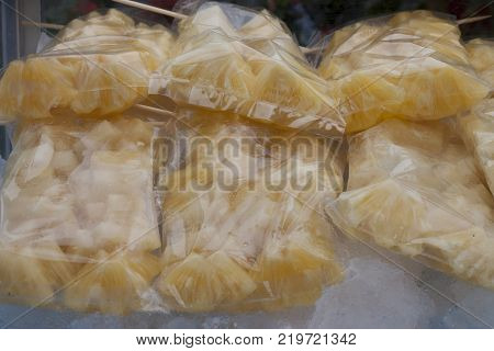 Pineapple is sliced in plastic bag In a glass cabinet with ice below. The fruit is suitable for hot weather.