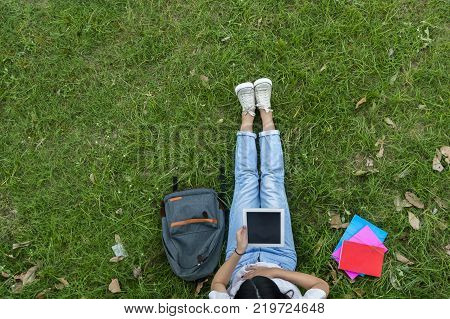 Top view of woman of students sitting together in the garden. University students doing group study.