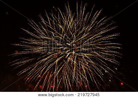 A volley of fireworks in the form of curved yellow arrows on a black night sky