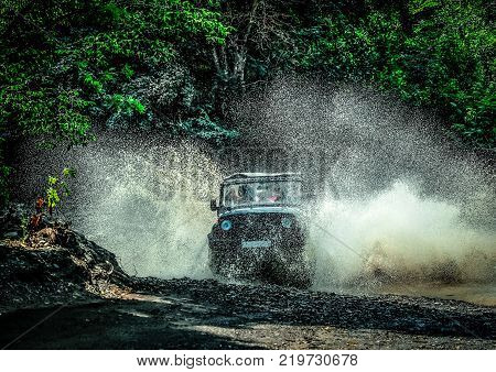 trip on an off-road vehicle. off-road car at high speed crosses a mountain stream