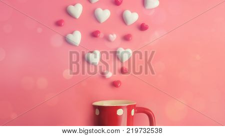 Floating valentines hearts over red coffee cup on pink background with copy space. Symbol of love. Happy Valentines Day background.Saint Valentine's Day concept. Can be used for celebrations valentines day.