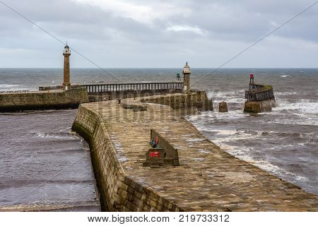 Whitby east and west pier lighthouses and harbour entrance beacons in the historical tourist resort of Whitby North Yorkshire England.
